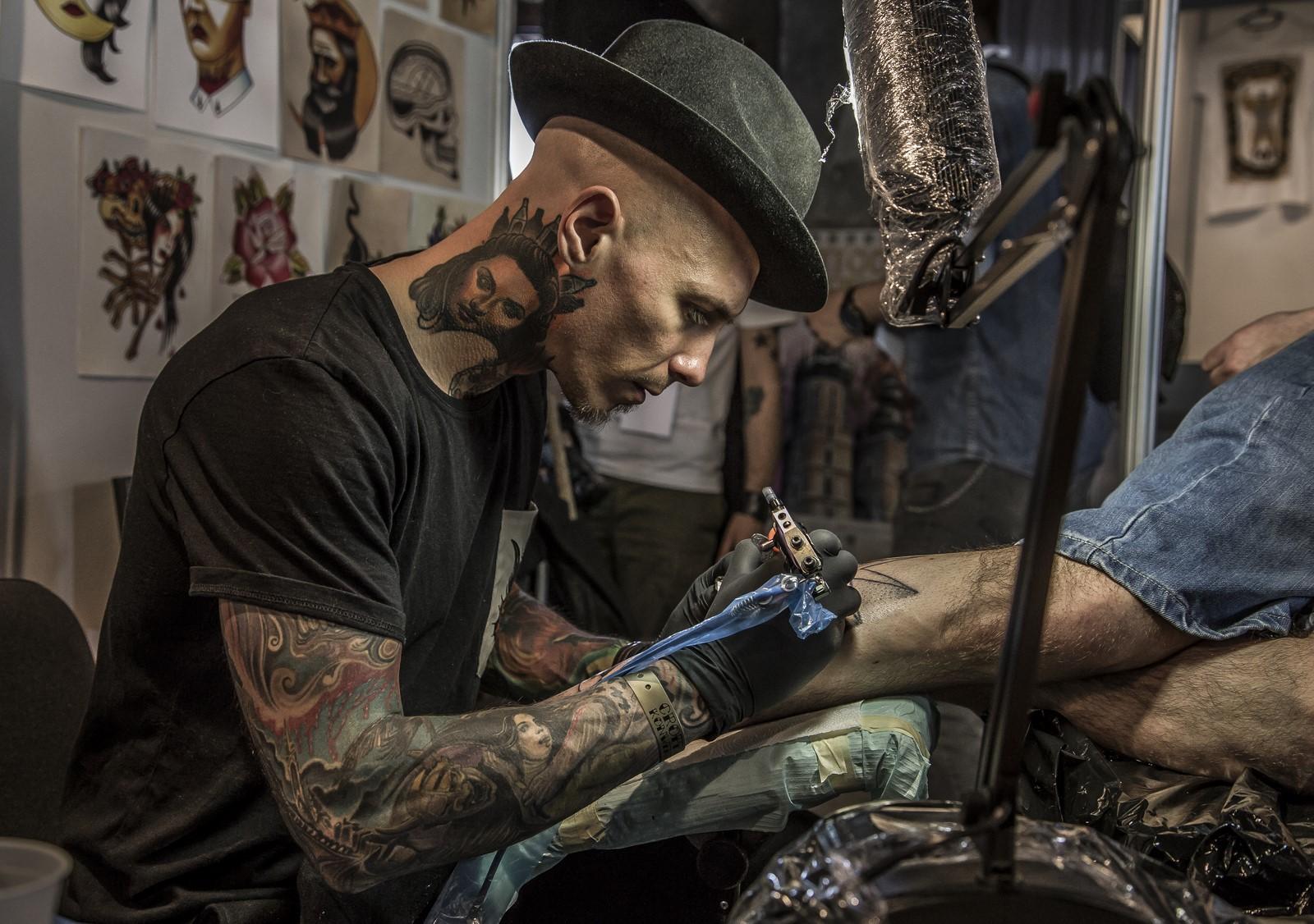 Mężczyzna w tatuażach, tatuujący czyjąś rękę