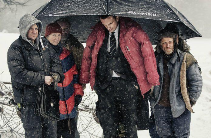 Grupa ludzi ubrana w kurski, stojąca pod dużym parasolem, dookoła pada śnieg