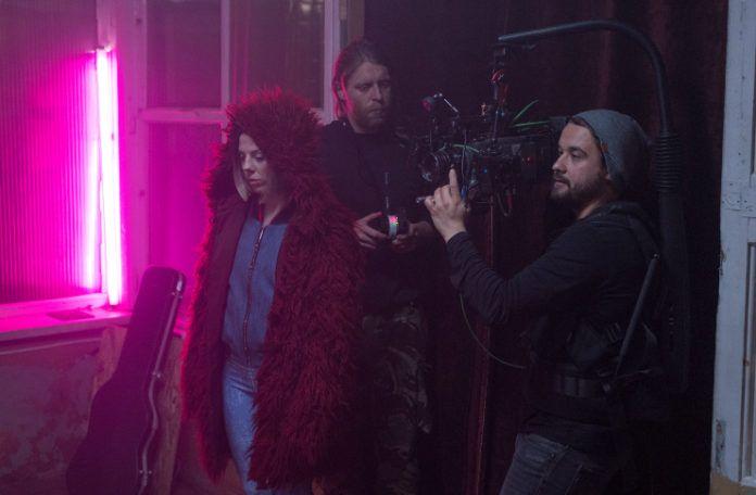 Dziewczyna w futrzastym płaszczu, za nią kamerzysta