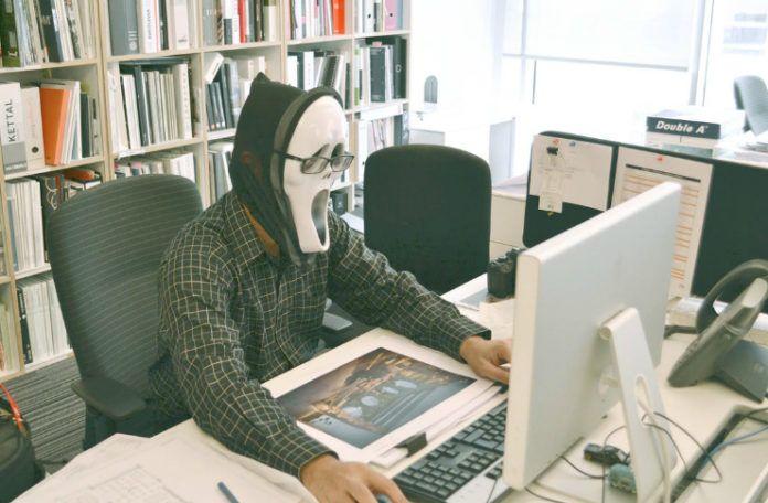 obrazek przestawia osobę siedzącą przed komputerem z założoną na twarz maską