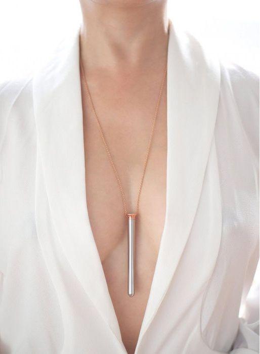 Piersi ubrane w biala koszule a miedzy nimi zawieszony naszyjnik w ksztalcie wibratora