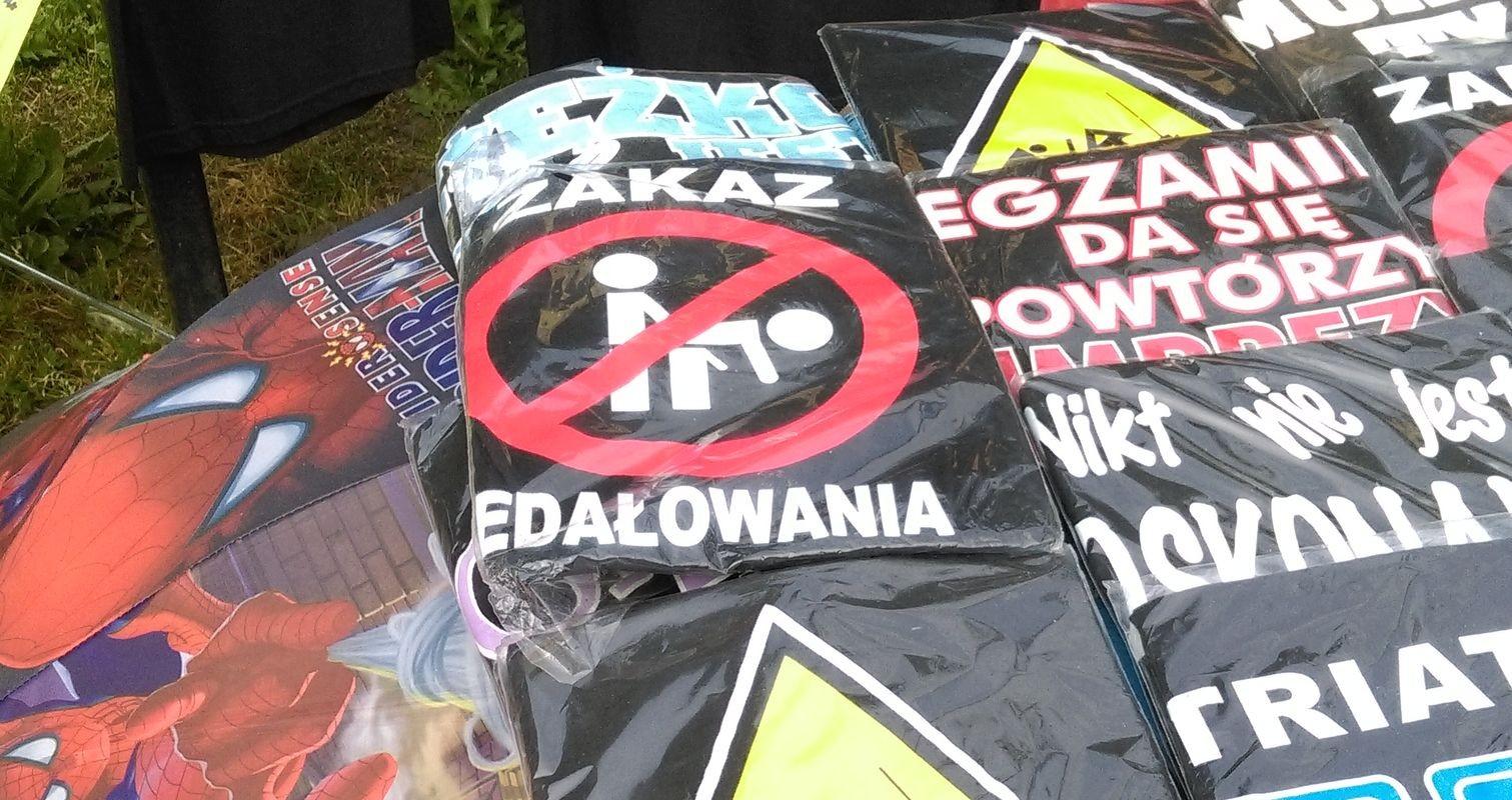 Widok zapakowanych w folie koszulek z napisami i grafikami