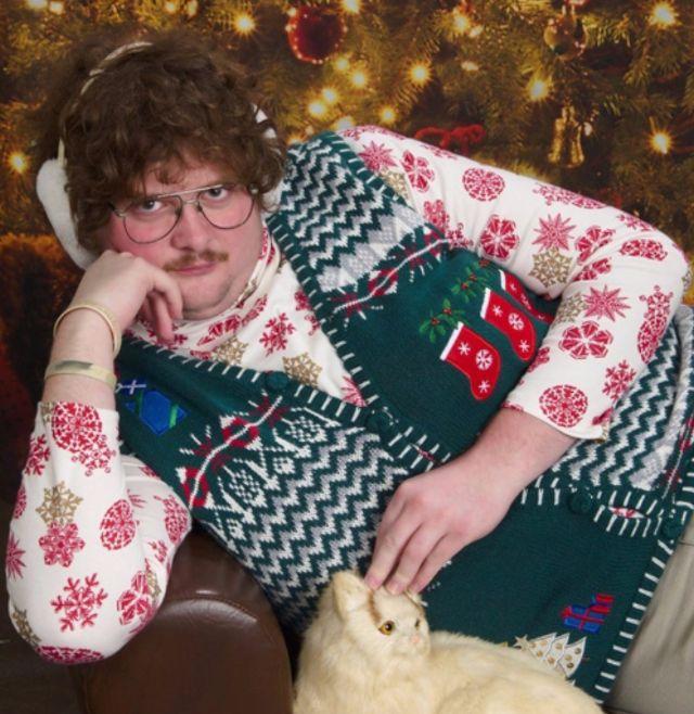 Portret mężczyzny ubranego w kwiecistą koszulę i świąteczny sweter, leżący z kotem na kanapie