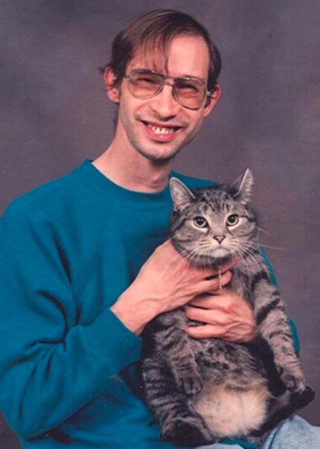 Mężczyzna w morskiej bluzie i okularach trzyma na rękach kota