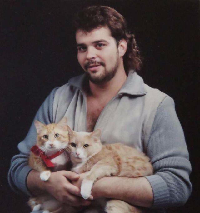 Mężczyzna w jeansowej lekko rozpiętej koszuli trzyma na rękach dwa koty