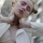 Dziewyczna ubrana w bialy biustnosz i białą marynarkę, trzyma dłonie na swojej szyi, w tle blokowisko