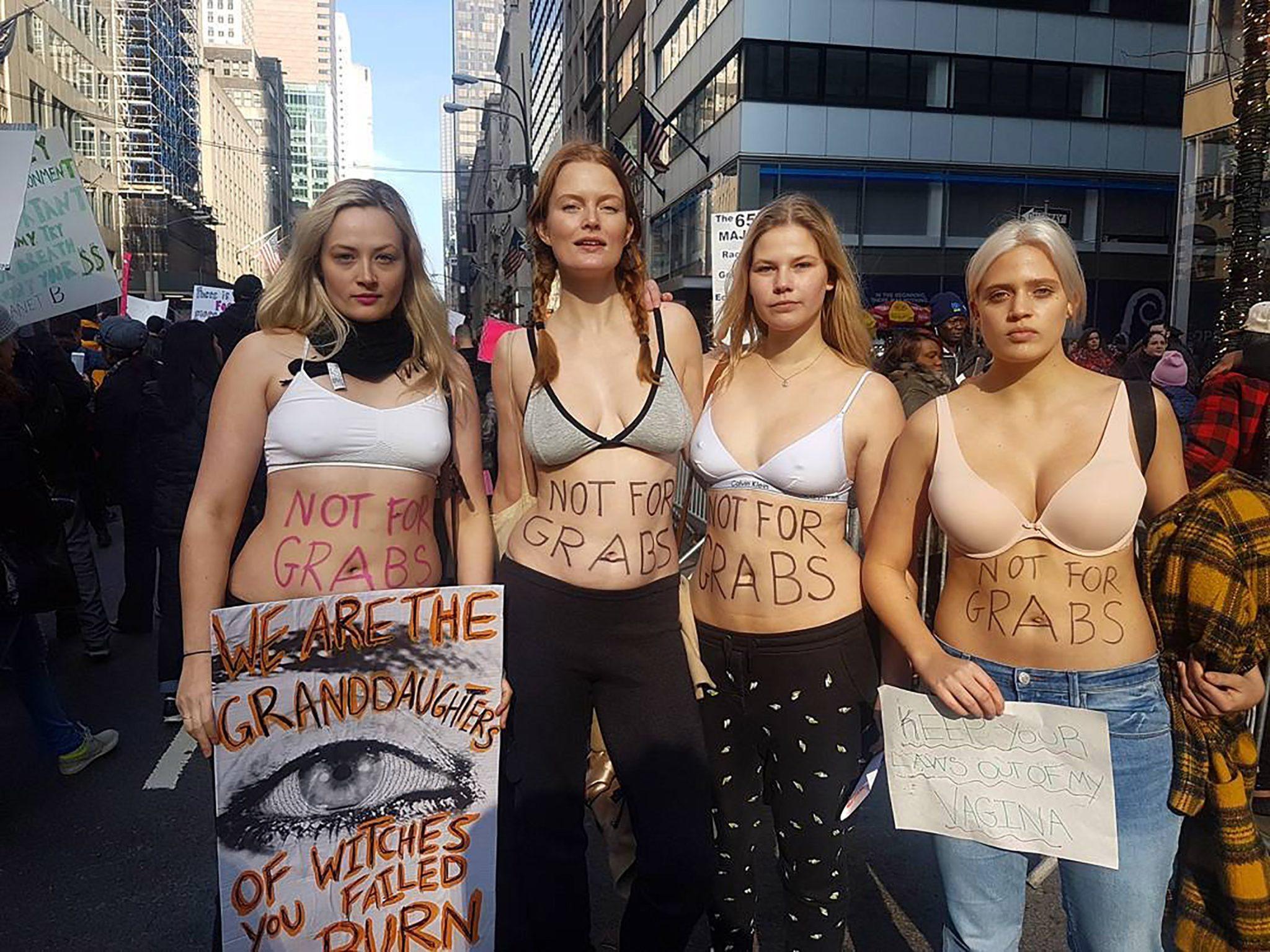 Cztery dziewczyny ubrane w spodnie i biustonosze na marszu
