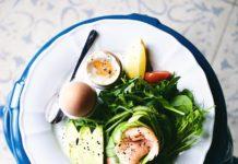 Jasny talerz z niebieskim obramowaniem, na którym są jajka i różne warzywa