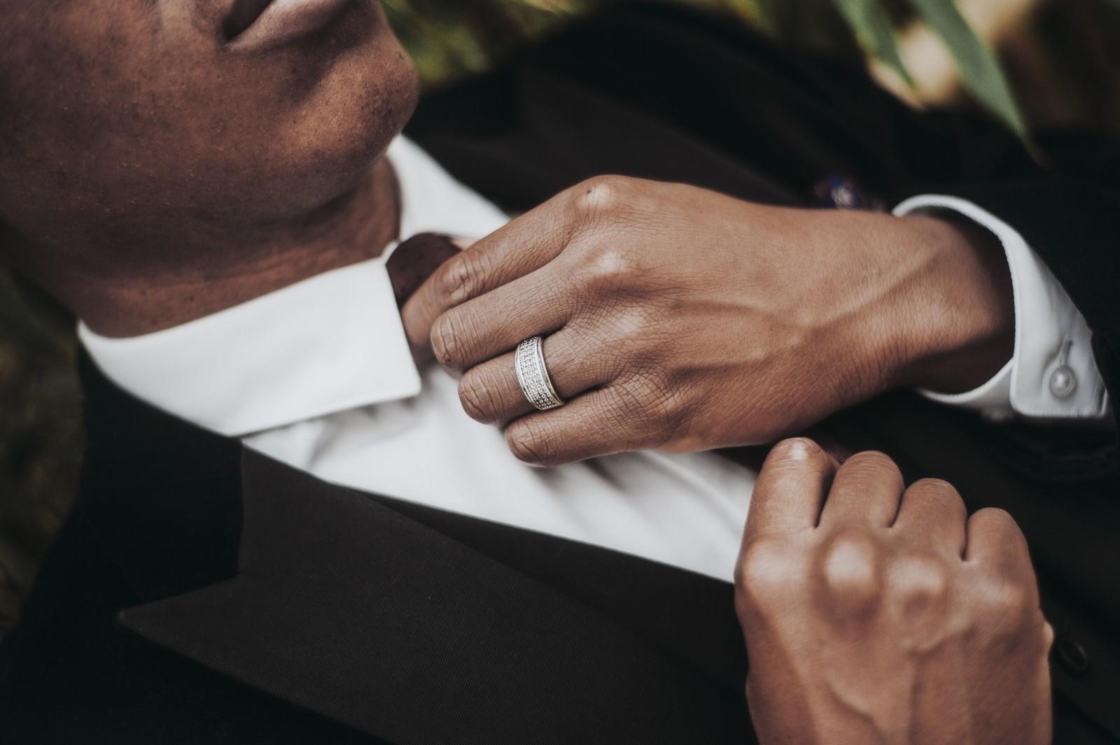 Mężczyzna poprawiający krawat przy garniturze