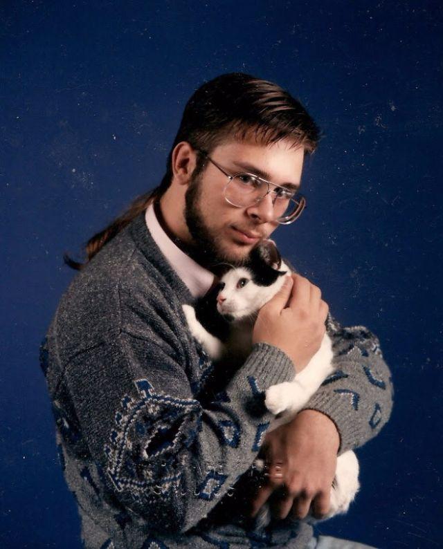 Portret mężczyzny ubranego w nerdowy sweter, przytulający kota