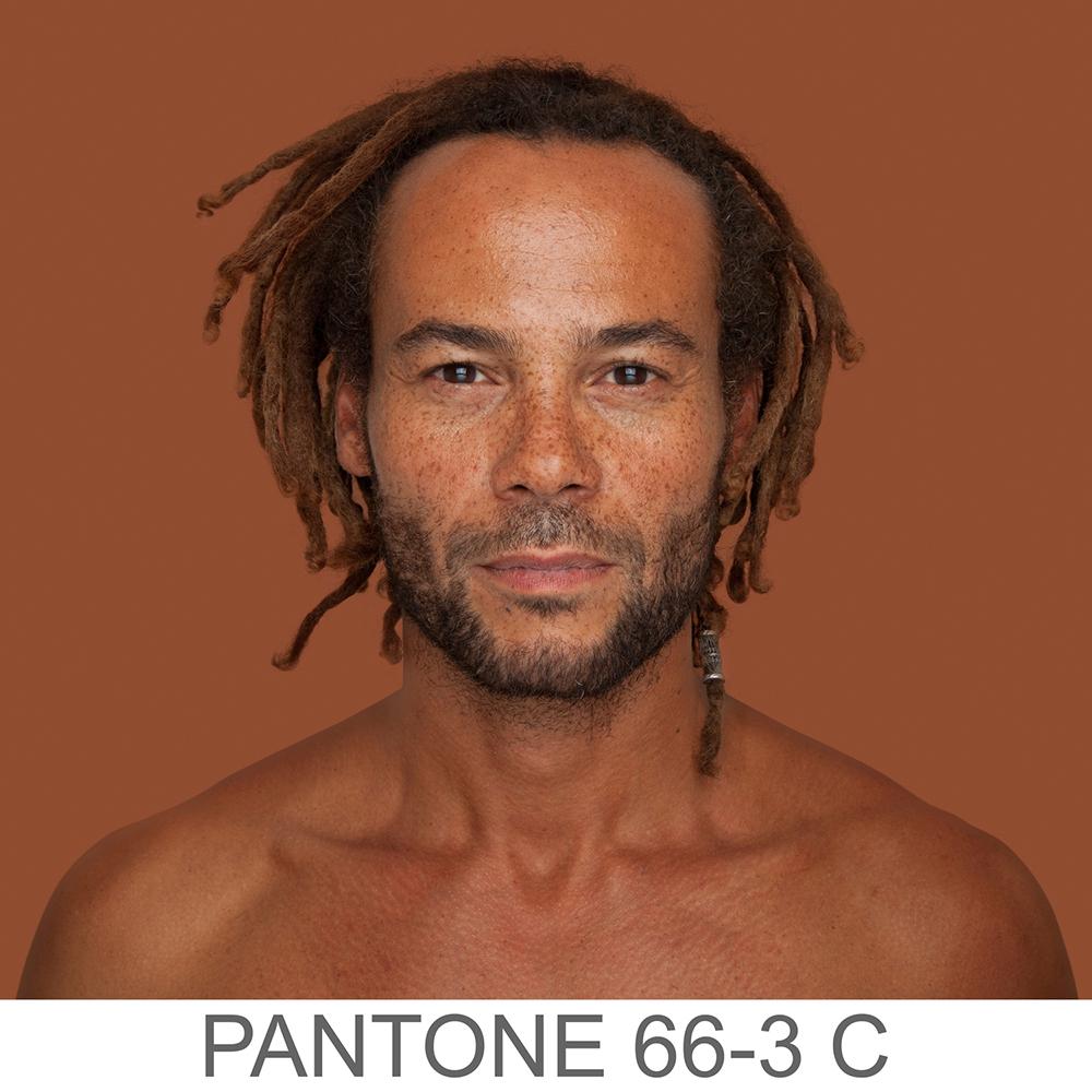 Fotografia portretowa kolorowa ukazująca mężczyznę o jasno-brązowym odcieniu skóry, drobnych dreadach i zaroście