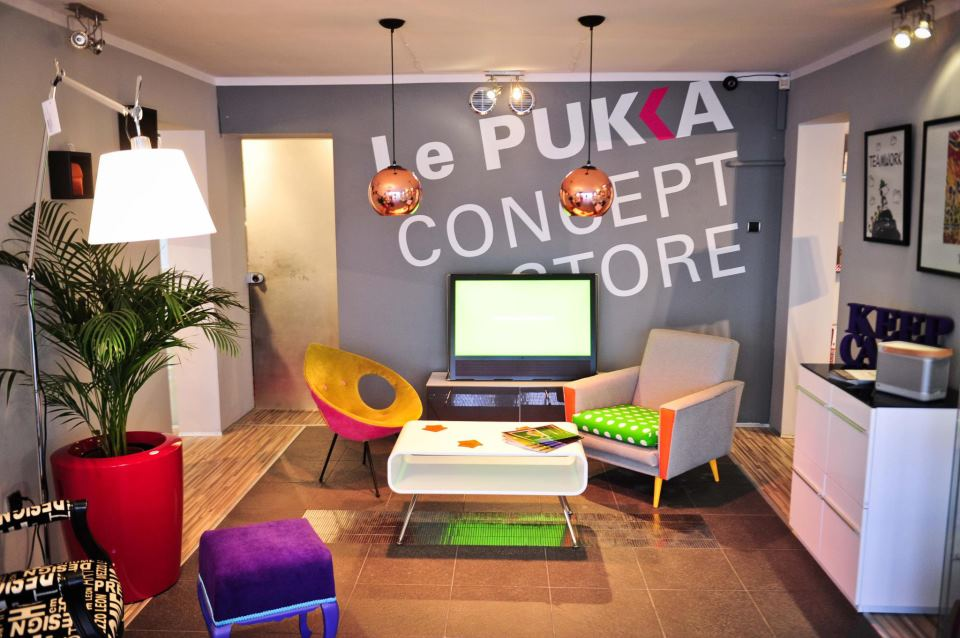Kolorowe wnętrze z napisem na ścianie Le Pukka Concept Store i kolorowymi fotelami