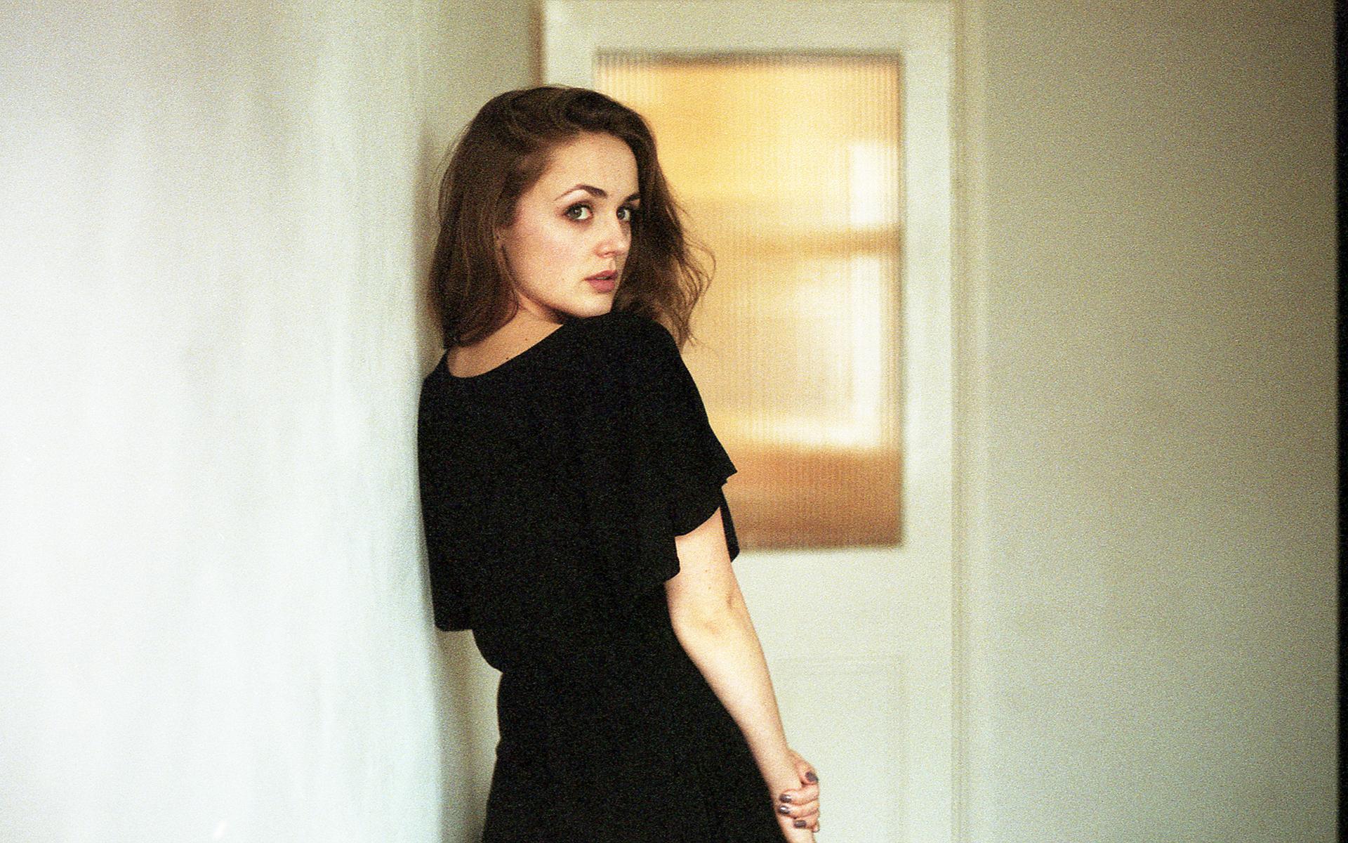 Dziewczyna stojąca tyłem w małej czarnej sukience