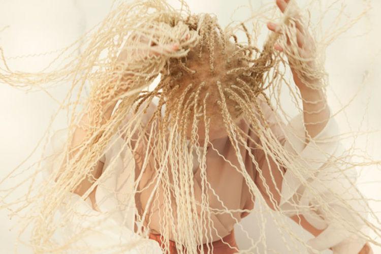 Na zdjęciu jedna z Albinosek macha głową, na której ma pełno drobnych warkoczyków.