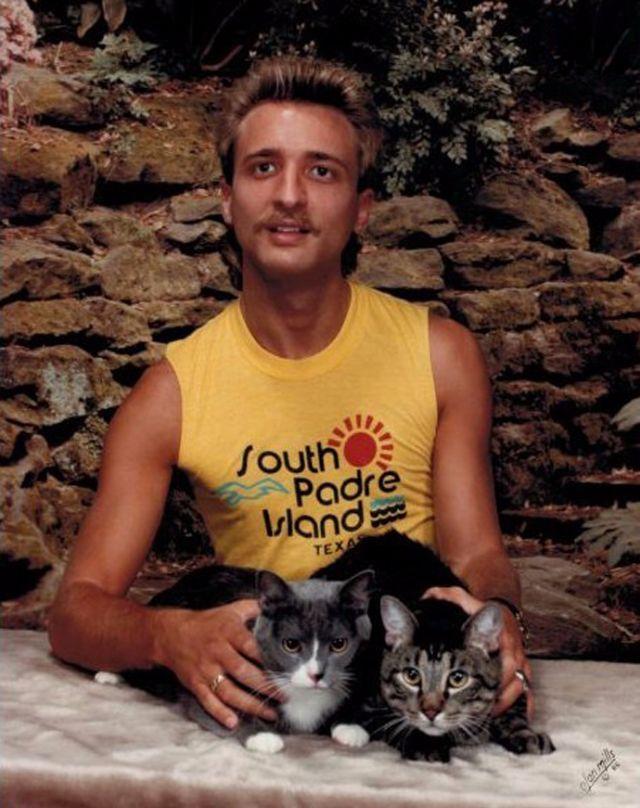 portret mężczyzny ubranego w żółty top, trzymający dłońmi dwa koty leżące na stole