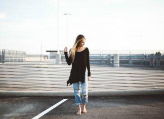 Dziewczyna stojąca boso na molo ubrana w poszarpane jeansy i czarną bluzkę