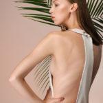 Dziewczyna, brunetka, stojąca na tle różowej ściany i liści palmy ubrana w białą bluzkę odkrywającą fragment pleców i cały bok