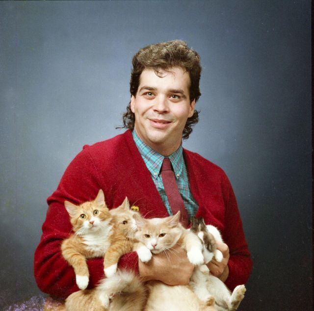 Portret mężczyzny w czerwonym swetrze, koszuli i krawacie, trzymający cztery koty