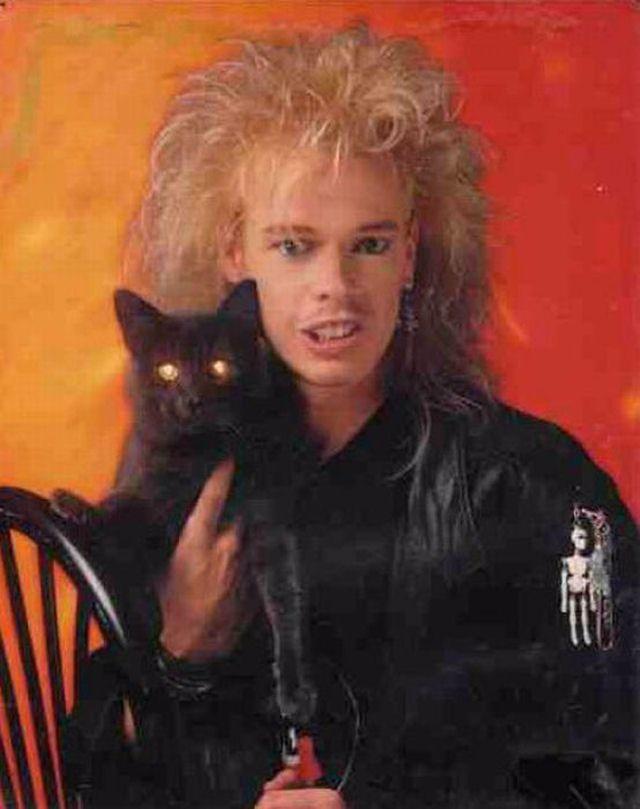 Mężczyzna ubrany w czarną skórę z natapirowanymi włosami, trzyma na ręku kota