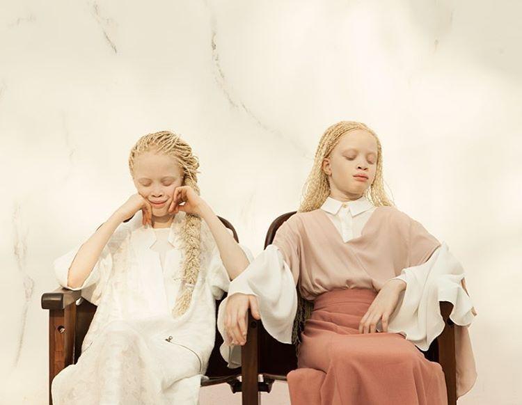 Dwie bliźniaczki siedzą na krzesłach i mają zamknięte oczy. Jedna lekko się uśmiecha i podpiera głowę rękoma. Druga ma ręce oparte na oparciach i ma lekko przechyloną głowę w bok i jest zamyślona.