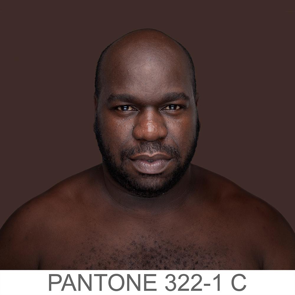 Fotografia portretowa kolorowa ukazująca mężczyznę o ciemno-brązowym kolorze skóry, ma szeroki noc i pełne usta. Posiada również zarost oraz drobny zarost na klatce piersiowej