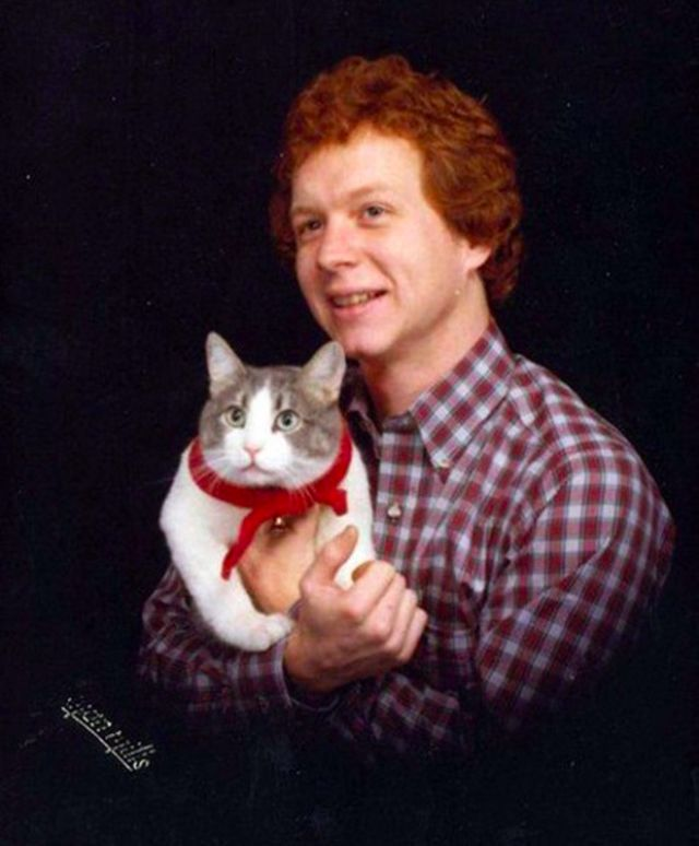 Mężczyzna w koszuli w kratę trzyma na rękach kota