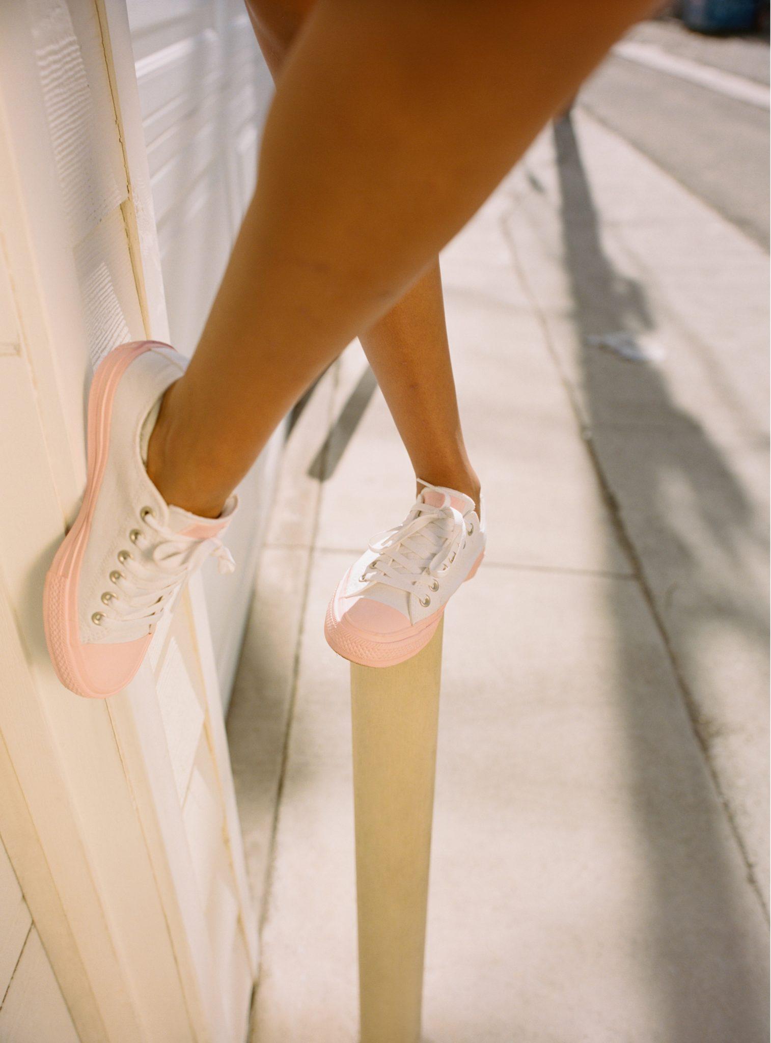 Nogi dziewczyny ubrane w pastelowo-białe trampki