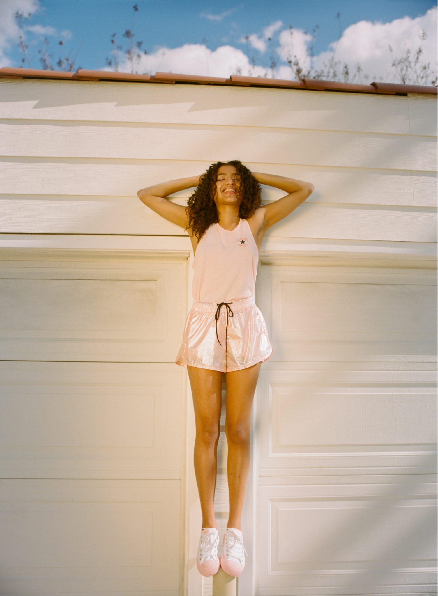 Dziewczyna ubrana w jasny kombinezon z szortami, na nogach ma trampki