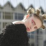 Dziewczyna ubrana w czarne futro, na głowie ma małe koczki, różowy makijaż, w tle jest budynek warszawskiej rotundy