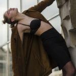 Dziewczyna ubrana w czarną spódnicę, biustonosz i płaszcz trzyma się jedną ręką elementu muru i wychyla się do tyłu
