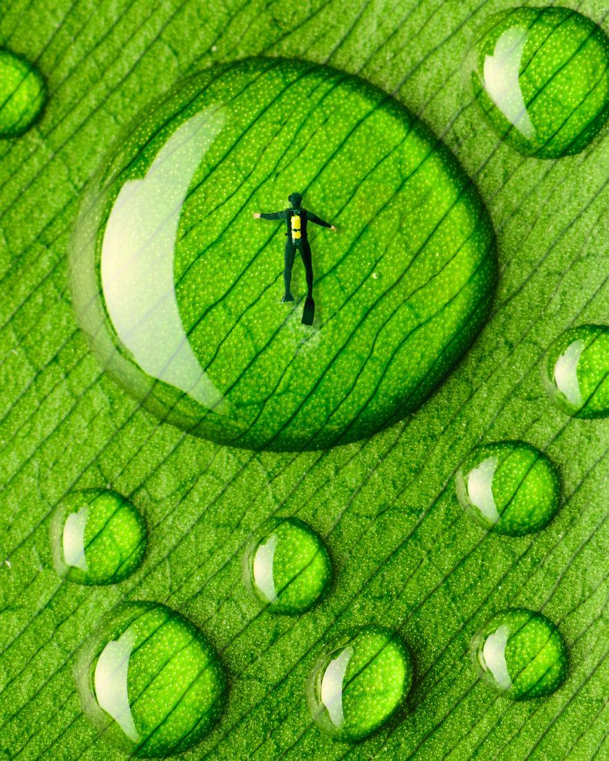 obraz przedstawia człowieka nurkującego w kropli wody znajdującej się na liściu
