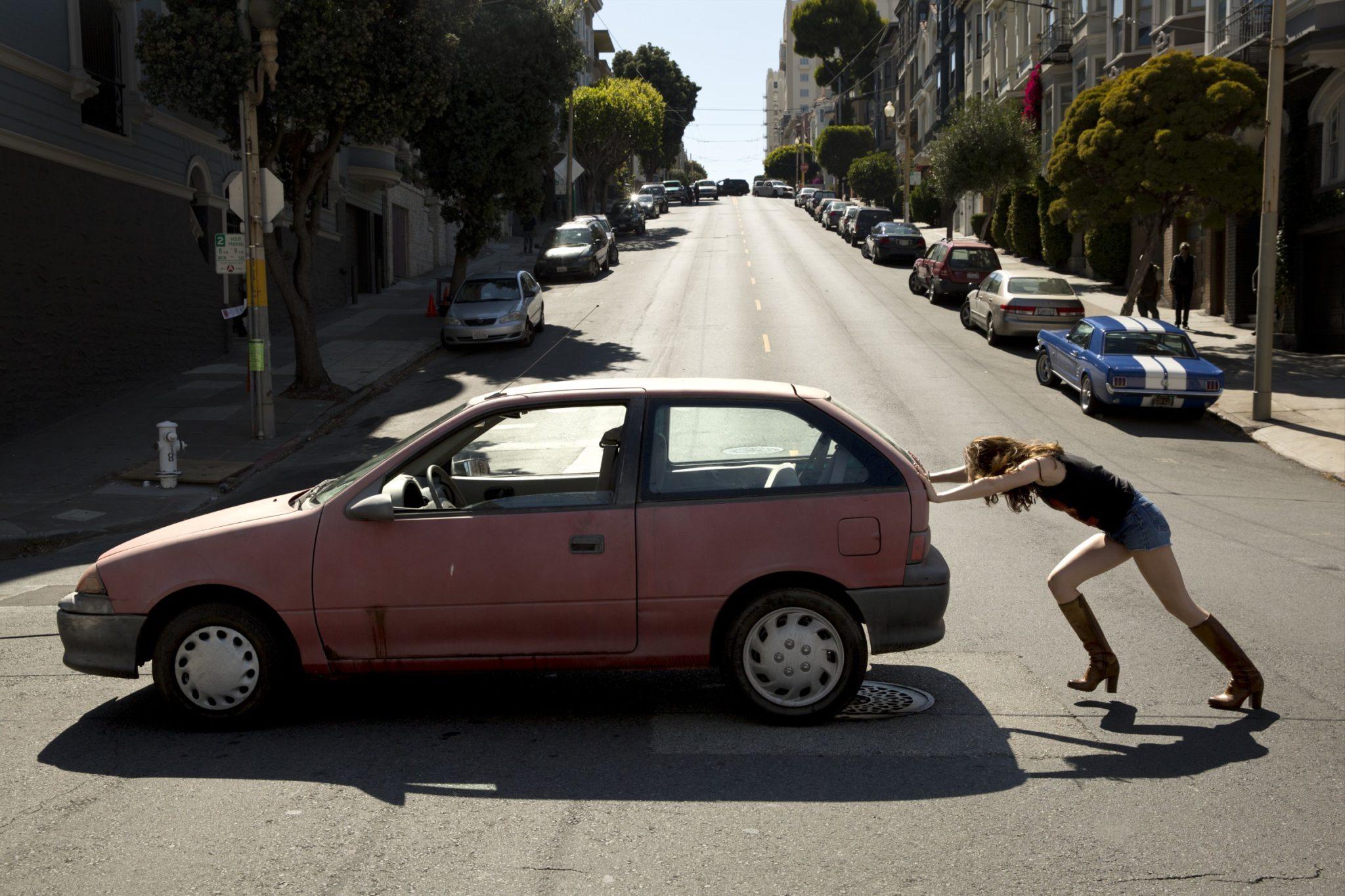 Dziewczyna pchająca samochód środkiem drogi