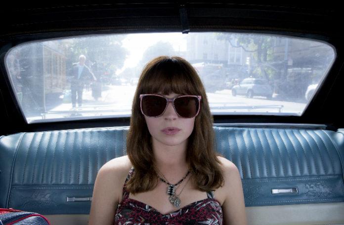Dziewczyna w ciemnych okularach siedzaca w samochodzie