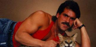 Portret mężczyzny ubranego w czerwony top leżącego z kotem obok