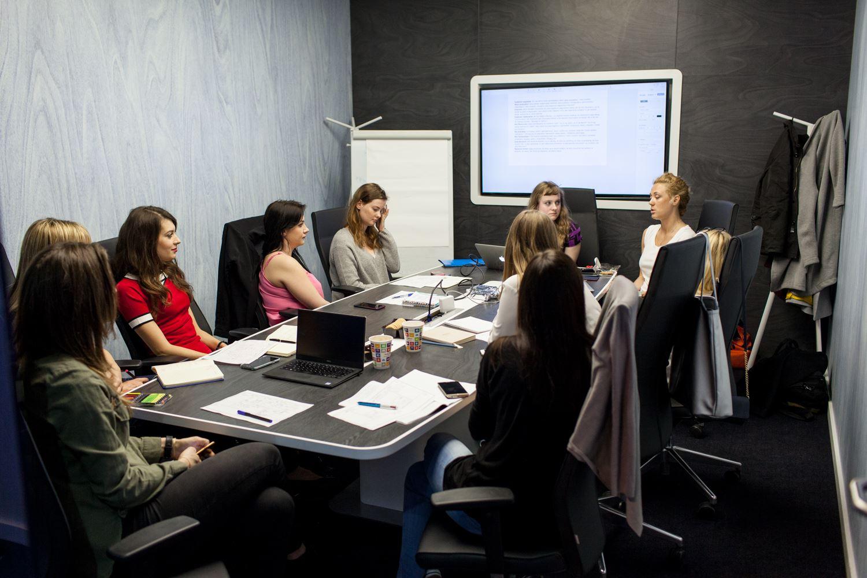 Grupa kobiet siedząca przy stole w sali konferencyjnej