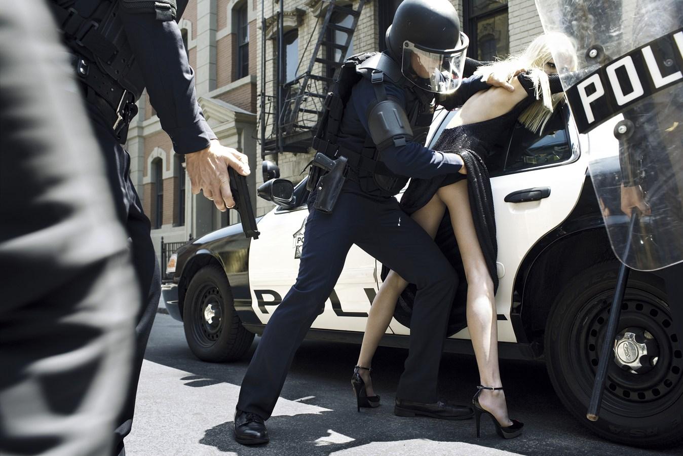 Fotografia czarno-biała. Kontrowersyjna fotografia mody ukazująca umundurowanego policjanta w kasku podczas zatrzymania kobiety. Kobieta, długowłosa blondynka, stojąca tyłem do widza, lecz jej wzrok skierowany jest wprost na oglądającego zdjęcie. Oparta o radiowóz, ubrana w błyszczącą długą sukienkę, z odkrytymi plecami oraz rozcięciem sięgającym i odsłaniającym prawy pośladek. Umundurowany policjant jedną ręką trzyma kobietę za prawe ramie,a prawą rękę wsuwa pod sukienkę i trzyma kobietę za odsłonięty pośladek. W kadrze częściowo widać jeszcze dwóch innych umundurowanych policjantów.