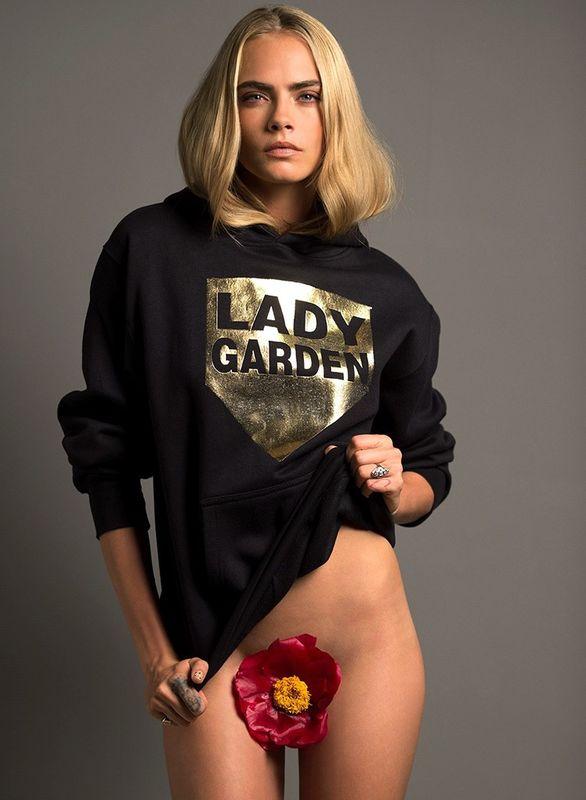 Blondynka pozuje w bluze i kwiatem między nogami
