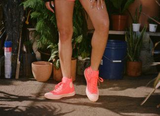 Nogi kobiety ubrane w różowo-czerwone trampki Converse