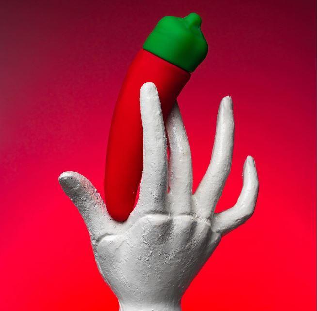 na obrazku znajduje się wibrator kształcie papryczki chilli i dotykająca go syntetyczna ręka