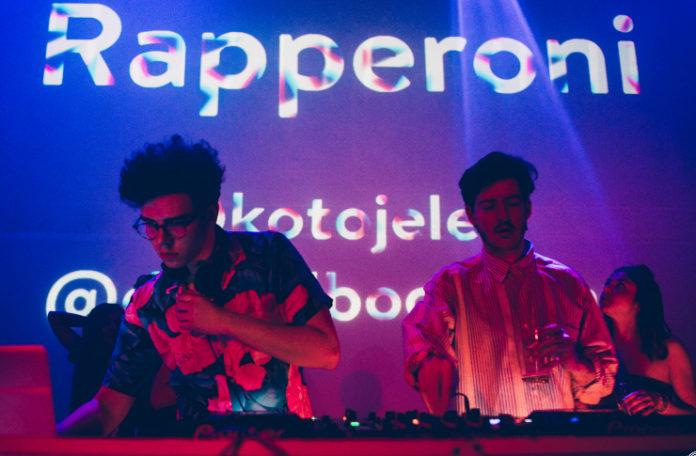 Dwóch mężczyzn stojących za DJskimi konsoletami