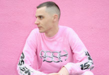 Mężczyzna ubrany na różowo na tle różowej ściany