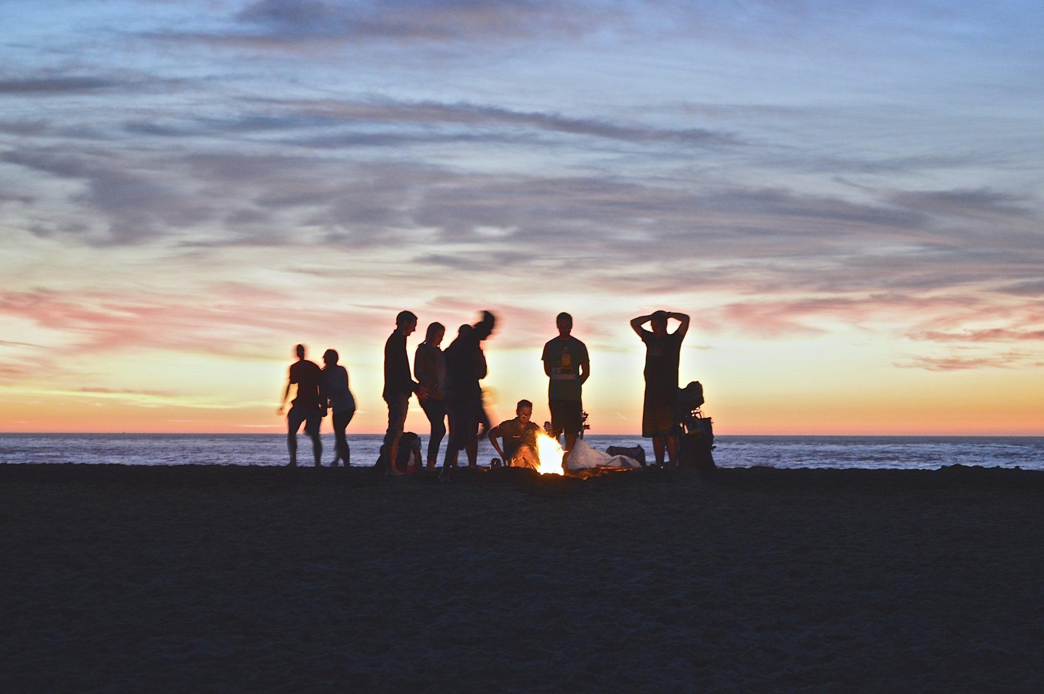 zdjęcie przedstawia grupkę ludzi palących ognisko na tle zachodzącego nad morzem słońca