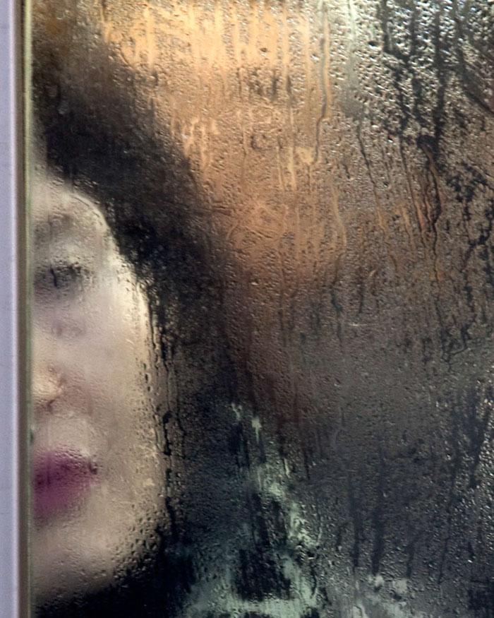 Kobieta w zatłoczonym metrze, ujęcie przez zaparowaną szybę
