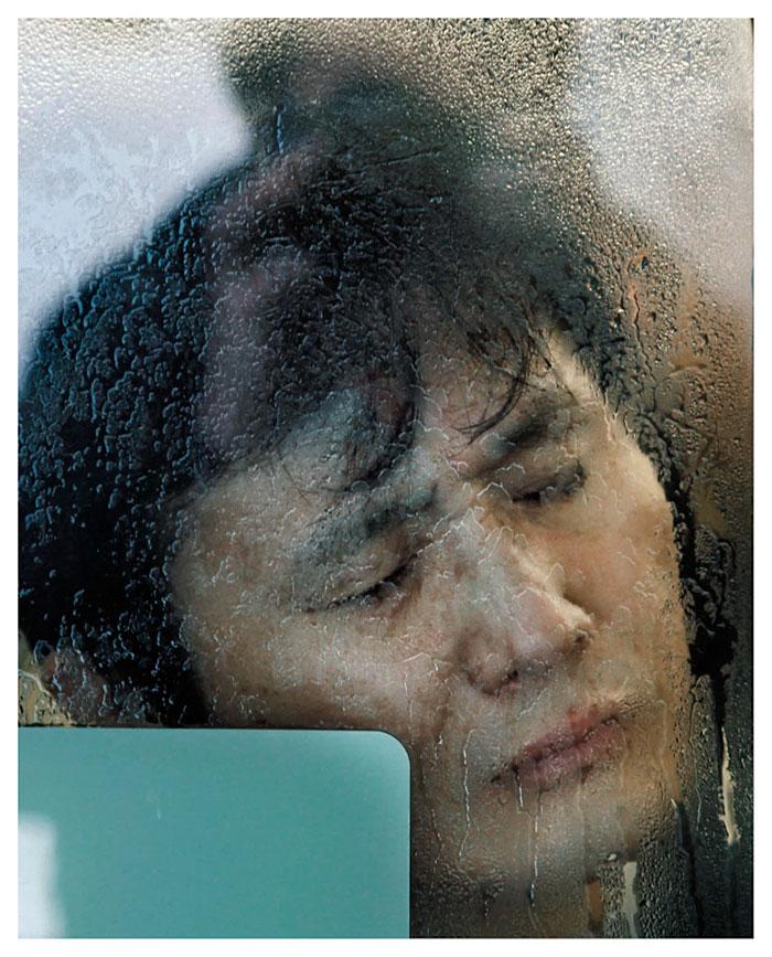 Mężczyzna z twarzą przy zaparowanej szybie w metrze