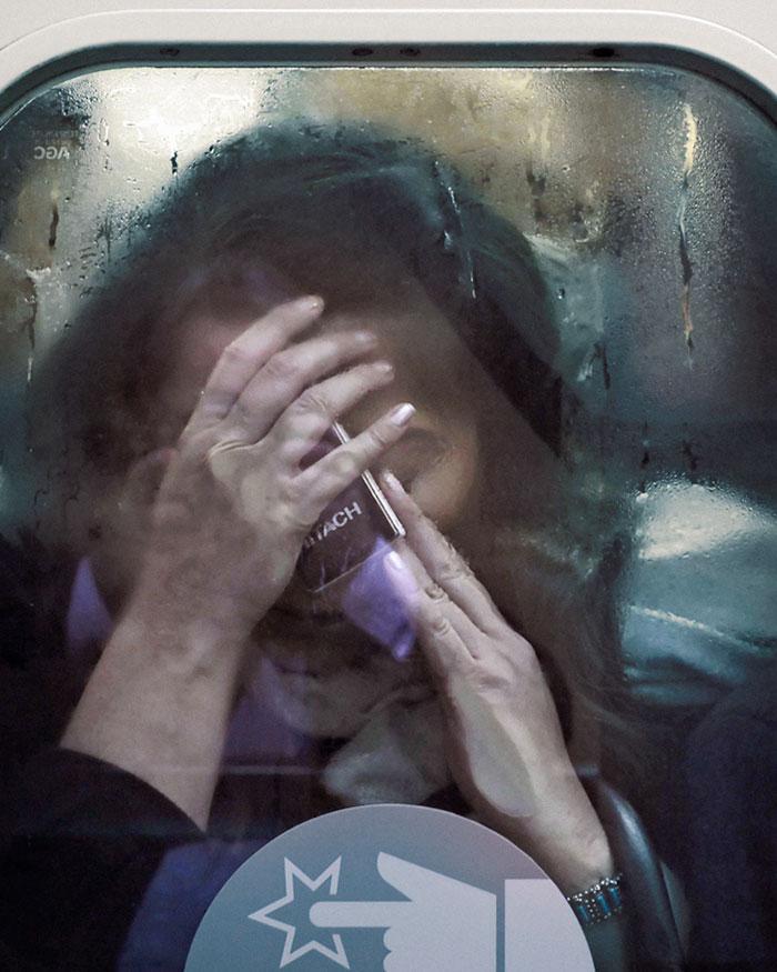 Kobieta w zatłoczonym metrze, trzymająca ręce na twarzy