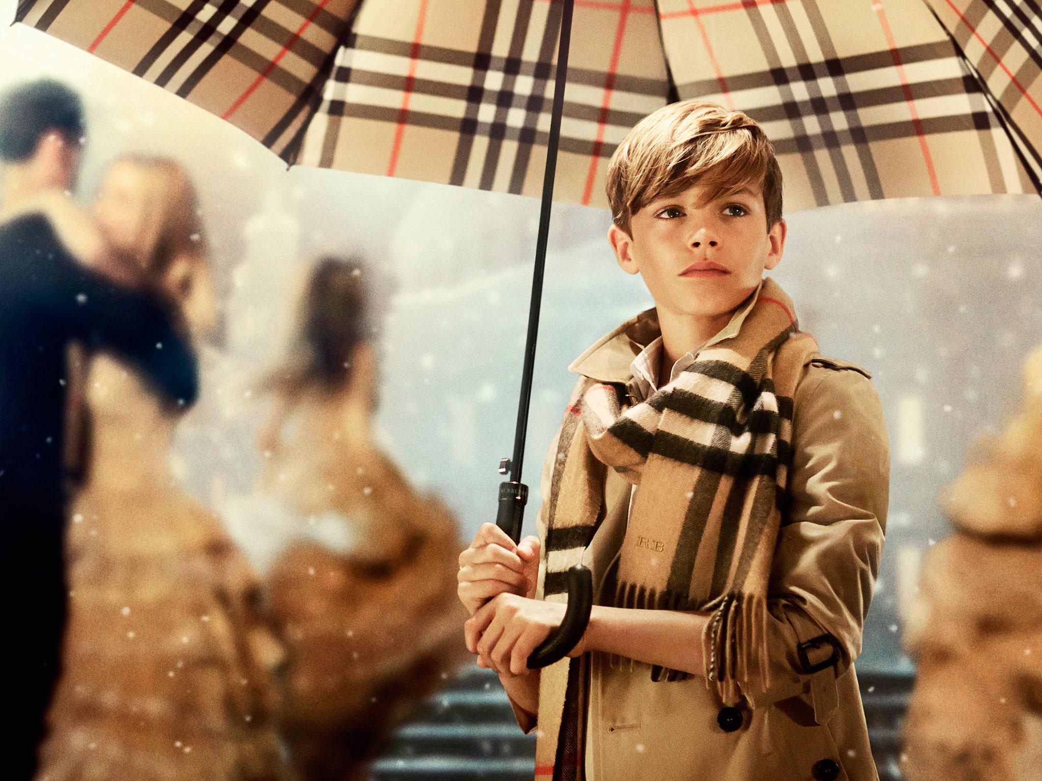 mlody chlopiec pozuje z parasolka ubrany w kultoy plaszcz burberry i szalik w kratke