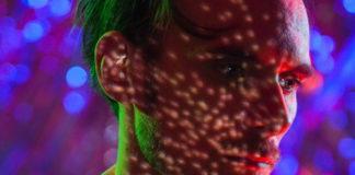 Mężczyzna, blondyn, który otoczony jest kolorowymi światłami