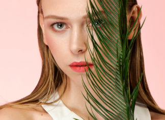 Portret dziewczyny trzymającej łodygę palmy na wysokości połowy twarzy