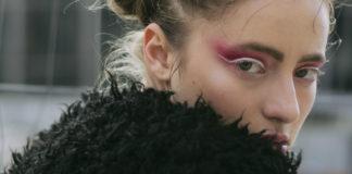 Portret dziewczyny z mocnym, różowym makijażem, ubranej w czarne futro