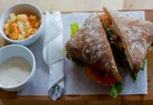 Na zdjęciu widzimy śniadanie jednej z restauracji, tj. bułkę z sałatą i pomidorami, sos w małym słoiczku oraz małą sałatkę w słoiczku, wszystko podane na drewnianej tacy ze sztućcami owiniętymi w serwetkę.